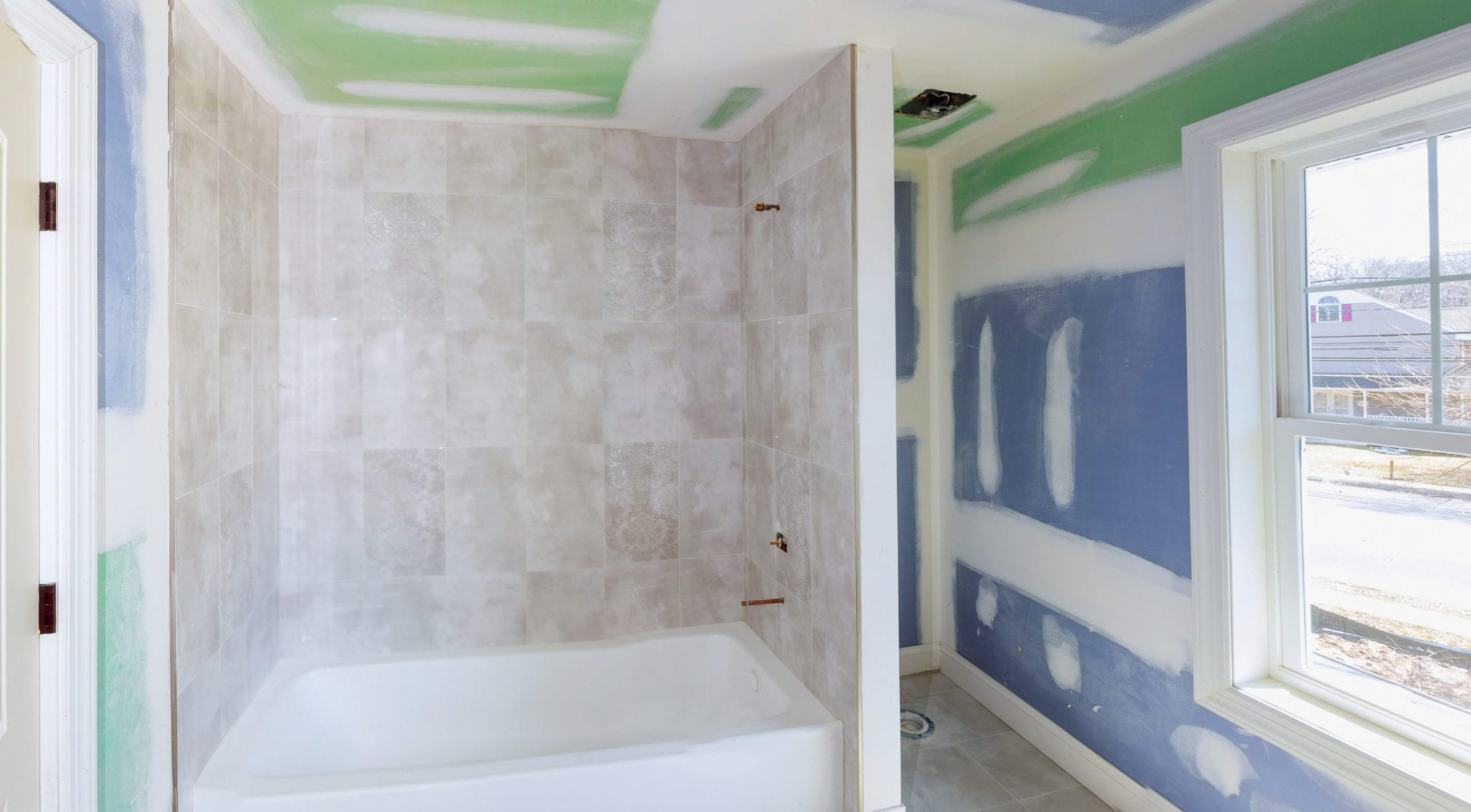 Bathroom remodel progresses as drywall is smoothed, covering seams and screws with tape and spackle mud