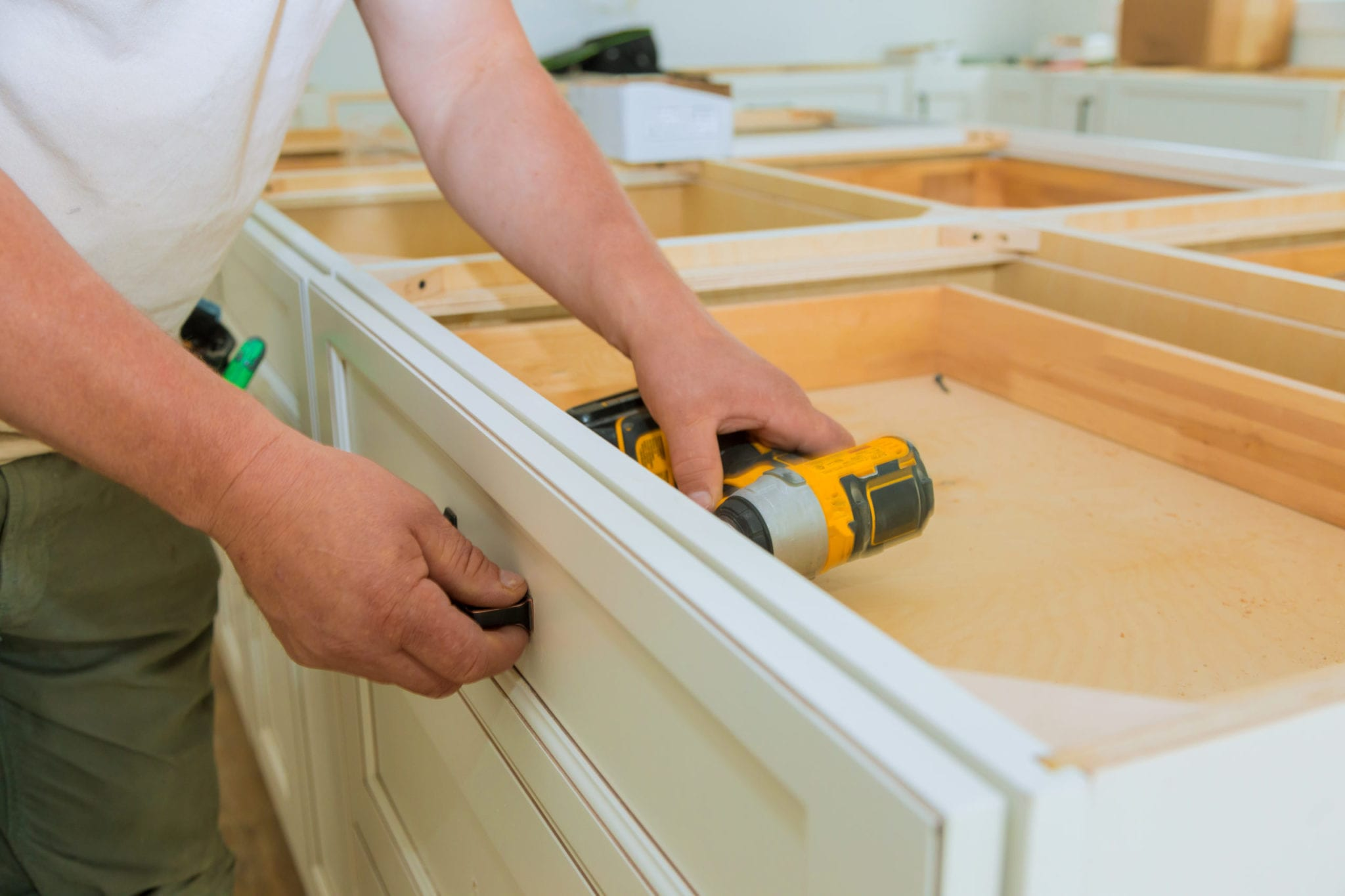 Installation of measuring drawers handles on kitchen cabinets