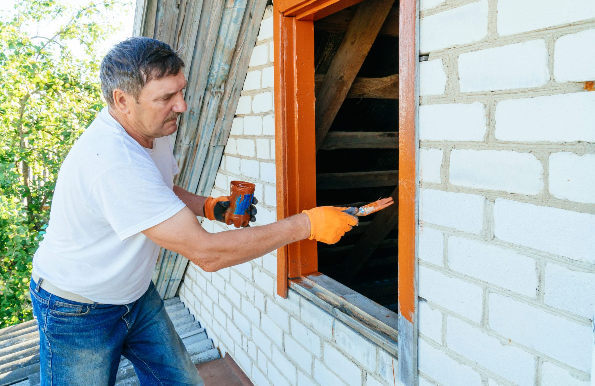 Senior man painting outside of painting wooden window exterior