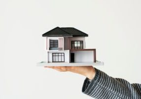 Hand presenting model house for home loan campaign